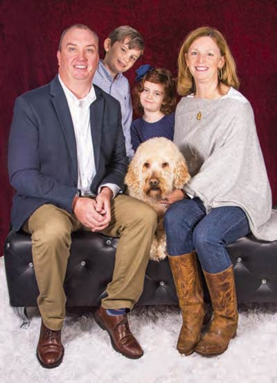 Jim and Melissa Kubu with Hank the goldendoodle and their two human children, Jamison and Olivia.