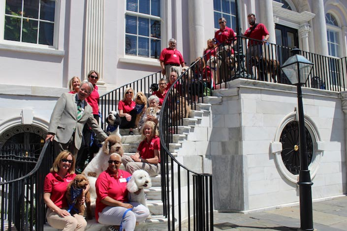 April 30, 2018: a few MUSC Therapy Dog teams took a group photo with the Honorable Mayor John Tecklenburg on the steps of City Hall after he honored our four legged therapists.