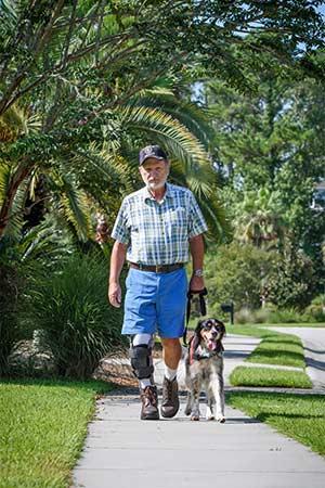 Service dog Sadie walks alongside John Beahm.